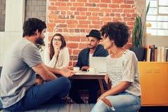 Gruppe Freunde, die an einem Café sitzen und sprechen Stockfotografie
