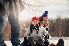 Gruppe Freunde, die einen Schlitten im Schnee im Winter ziehend genießen Stockfoto