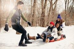 Gruppe Freunde, die einen Schlitten im Schnee im Winter ziehend genießen Lizenzfreie Stockbilder