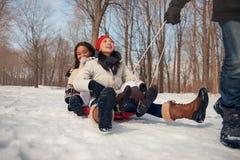 Gruppe Freunde, die einen Schlitten im Schnee im Winter ziehend genießen Stockfotos