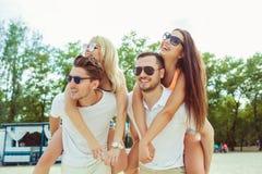 Gruppe Freunde, die entlang den Strand gehen, wenn die Männer piggyback den Freundinnen Fahrt geben Stockfotos