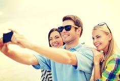 Gruppe Freunde, die Foto mit Smartphone machen Stockfotografie