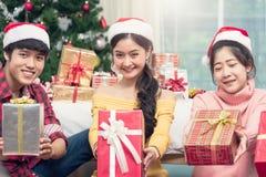 Gruppe Freunde, die Geschenkbox zeigend feiern stockfotos