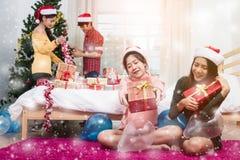 Gruppe Freunde, die Geschenkbox zeigend feiern stockbild