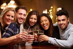 Gruppe Freunde, die Getränke in der Bar glättend genießen Lizenzfreies Stockfoto