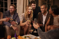 Gruppe Freunde, die Getränke und Snäcke an der Partei genießen stockfotografie