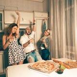 Gruppe Freunde, die Getränke glättend und an Haus-PA tanzend genießen Lizenzfreie Stockbilder