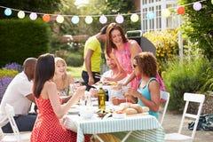 Gruppe Freunde, die Grill im Freien zu Hause haben Lizenzfreies Stockbild