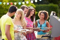 Gruppe Freunde, die Grill im Freien zu Hause haben Lizenzfreie Stockfotos