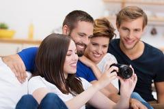 Gruppe Freunde, die heraus ein Foto überprüfen Stockfotografie