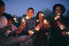 Gruppe Freunde, die heraus mit Wunderkerzen genießen Stockfotos