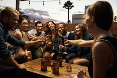Gruppe Freunde, die heraus Nacht an der Dachspitzen-Bar genießen lizenzfreie stockbilder