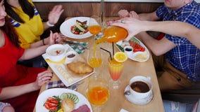 Gruppe Freunde, die im Café zu Mittag essen Tabelle voll der verschiedenen Nahrung und der Getränke stockfoto