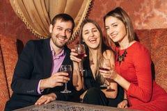 Gruppe Freunde, die im Restaurant stillstehen Stockbilder