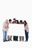 Gruppe Freunde, die leeres Zeichen zusammenhalten Lizenzfreies Stockbild