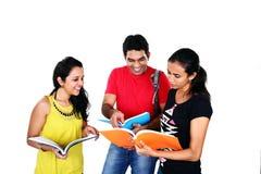 Gruppe Freunde, die, lokalisiert auf Weiß studieren. Lizenzfreies Stockbild