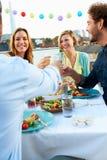 Gruppe Freunde, die Mahlzeit auf Dachspitzen-Terrasse essen Lizenzfreie Stockbilder