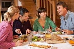 Gruppe Freunde, die Mahlzeit im alpinen Chalet genießen Stockbilder