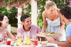 Gruppe Freunde, die Mahlzeit outdoorss genießen Lizenzfreie Stockbilder