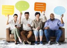 Gruppe Freunde, die mit einer Spracheblase sitzen Stockfotos