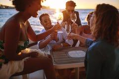 Gruppe Freunde, die mit Getränken an der Bootspartei zujubeln stockfotografie