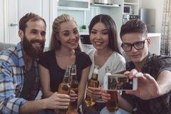 Gruppe Freunde, die Partei zusammen zu Hause haben Lizenzfreie Stockfotos
