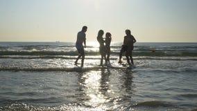 Gruppe Freunde, die in Richtung zum Meer laufen und mit ihren Füßen im kalten Wasser tanzen stock footage