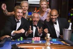 Gruppe Freunde, die am Roulettetisch feiern Lizenzfreies Stockbild