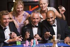 Gruppe Freunde, die am Roulettetisch spielen Lizenzfreies Stockfoto
