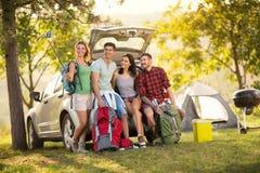 Gruppe Freunde, die selfie mit Smartphone auf Camping-Ausflug nehmen Lizenzfreie Stockbilder