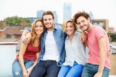 Gruppe Freunde, die sich zusammen auf Dachspitzen-Terrasse entspannen Lizenzfreie Stockfotografie