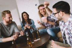 Gruppe Freunde, die Spaß während Spielkarten haben lizenzfreie stockfotografie