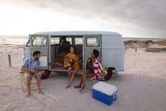 Gruppe Freunde, die am Strand bei der Stellung nahe Reisemobil genie?en stockfotografie