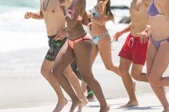 Gruppe Freunde, die am Strand an einem sonnigen Tag laufen und genießen lizenzfreies stockfoto