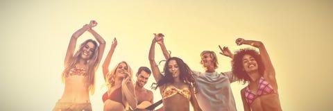 Gruppe Freunde, die am Strand während des Sonnenuntergangs tanzen stockfotos