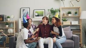 Gruppe Freunde, die traurigen jungen Mann auf dem Geburtstag den Kuchen-Gesang holend beglückwünschen stock video