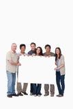 Gruppe Freunde, die unbelegtes Zeichen zusammenhalten Lizenzfreie Stockfotos