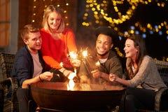 Gruppe Freunde, die Wunderkerzen durch Firepit beleuchten Stockfotos
