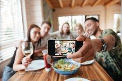 Gruppe Freunde, die zu Abend essen und selfie mit Smartphone nehmen lizenzfreie stockfotos