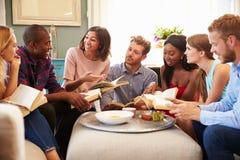 Gruppe Freunde, die zu Hause an der Buchgemeinschaft teilnehmen stockfotografie