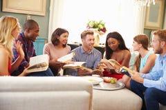 Gruppe Freunde, die zu Hause an der Buchgemeinschaft teilnehmen stockbilder