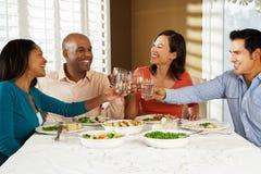 Gruppe Freunde, die zu Hause Mahlzeit genießen Lizenzfreie Stockfotografie