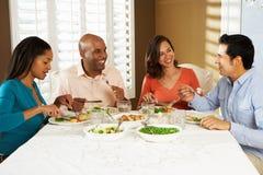 Gruppe Freunde, die zu Hause Mahlzeit genießen Stockfotos