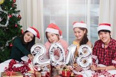 Gruppe Freunde, die zu Hause Weihnachten feiern und 2018 zeigen stockfoto