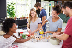 Gruppe Freunde, die zusammen Frühstück in der Küche kochen lizenzfreie stockbilder