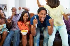 Gruppe Freunde, die zusammen im Sofa Watching Fernsehen sitzen Lizenzfreies Stockbild