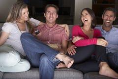 Gruppe Freunde, die zusammen im Sofa Watching Fernsehen sitzen Lizenzfreie Stockfotos