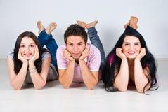 Gruppe Freunde in einer Reihe, die auf Fußboden liegt Stockbilder