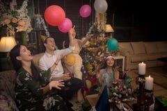 Gruppe Freunde feiern Weihnachten und neues Jahr zusammen und Ballone spielend Stockbilder