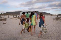 Gruppe Freunde kommen vom Strand zur?ck, um ihr Reisemobil zu verbinden lizenzfreie stockfotografie